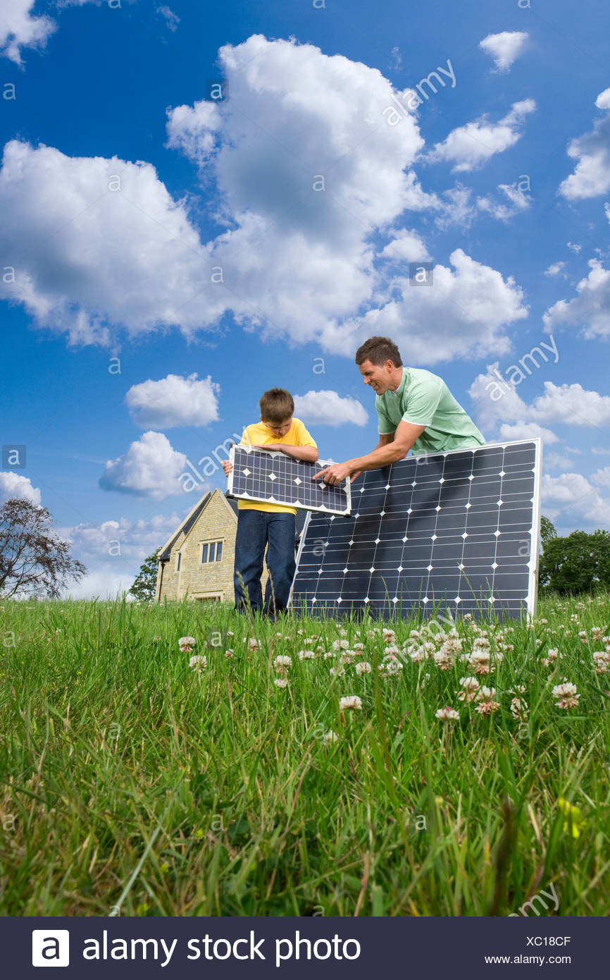 Man and boy holding solar panels in yard - Stock Image