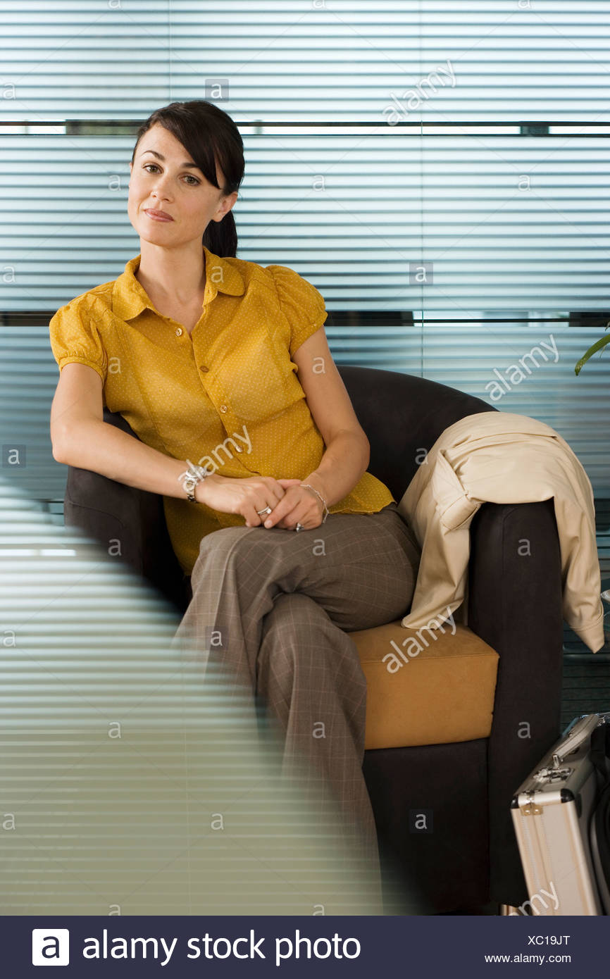 Confident businesswoman in yellow short sleeved blouse sitting in office chair portrait - Stock Image