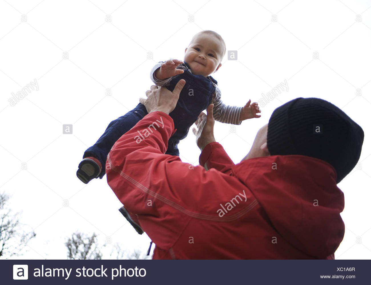 Father baby people throws up man parent paternity jacket red cap headgear love luck feelings emotion fun plays happiness child - Stock Image