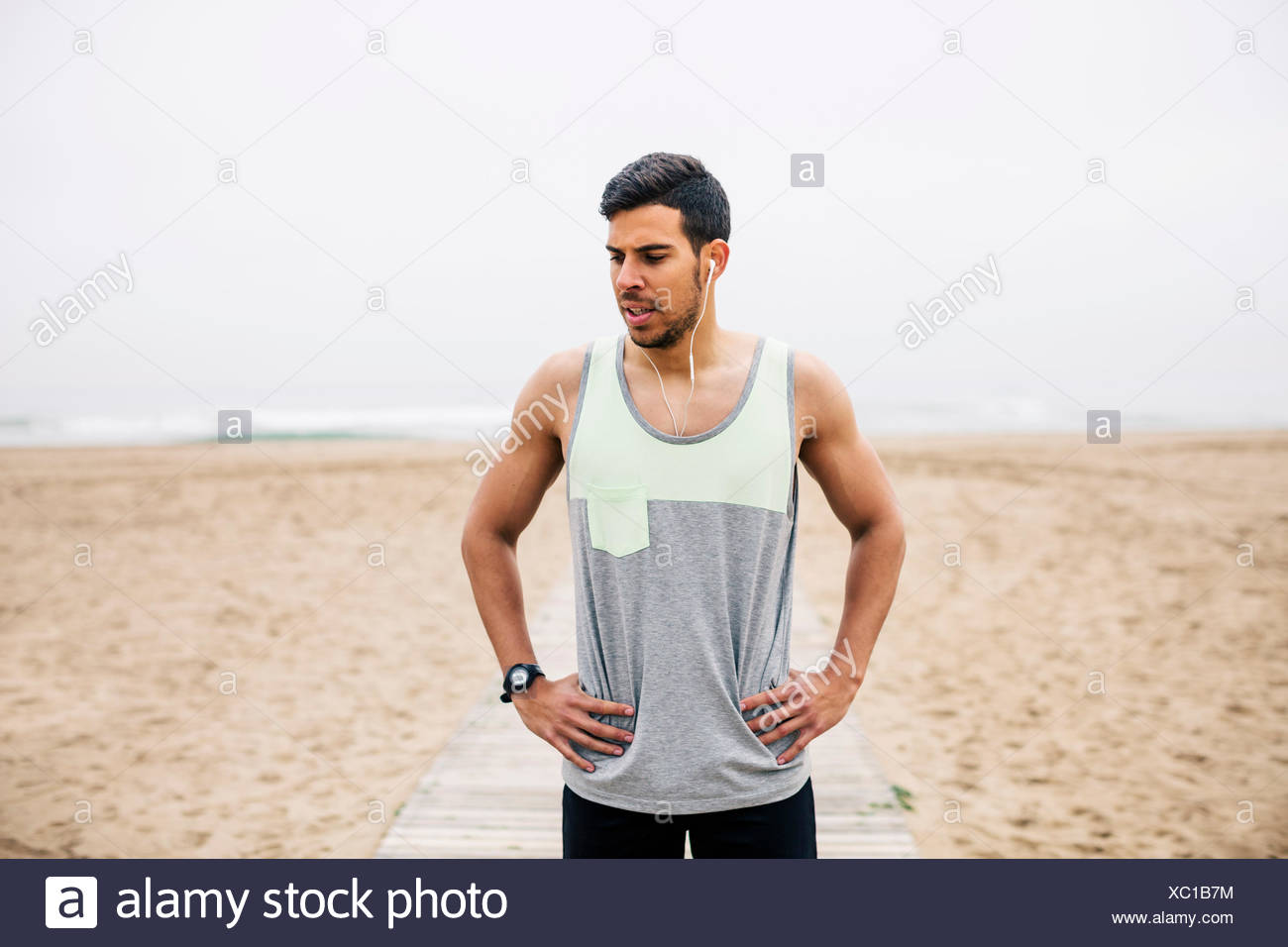 Portrait of athlete with earbuds on the beach - Stock Image