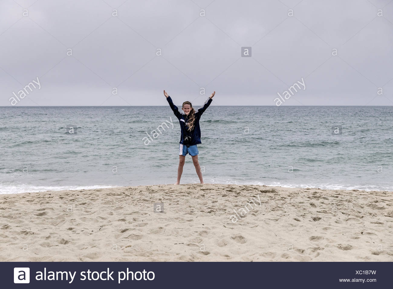 Joyous girl in bathing suit and open arms at the beach. - Stock Image