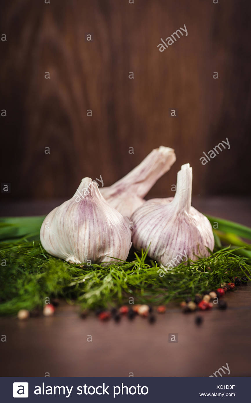 Garlic, herbs and spices on a wooden table - Stock Image