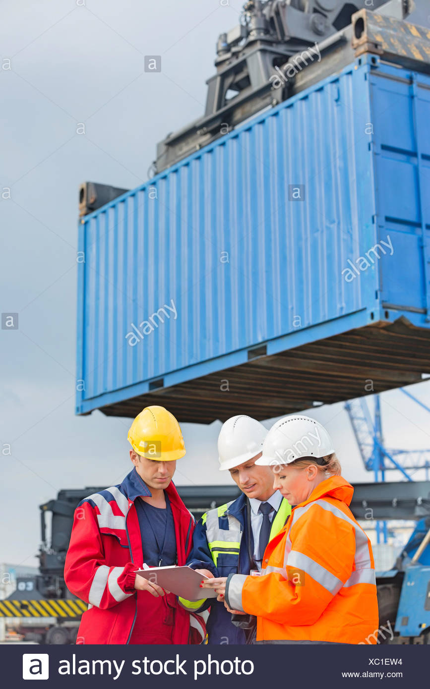 Workers discussing over clipboard in shipping yard - Stock Image