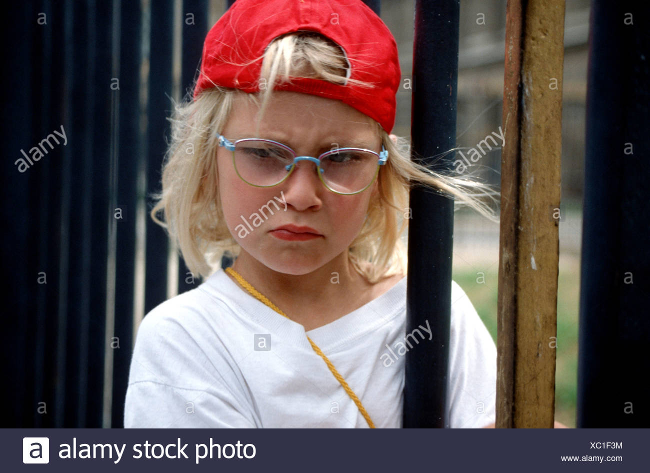 Toddler tantrum: Frustrated little girl with eye glasses pouting. - Stock Image