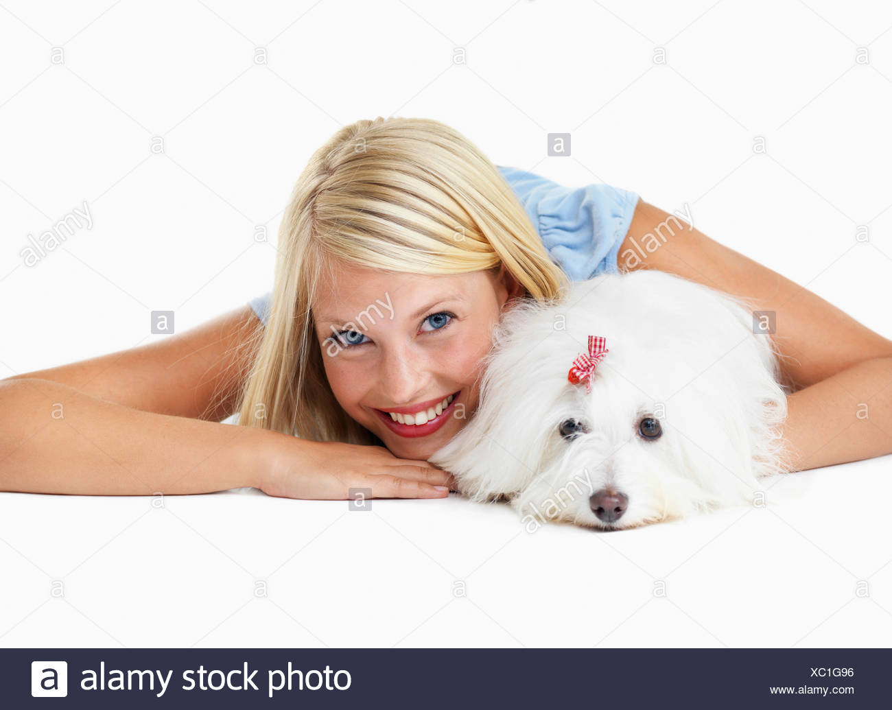 Studio Shot, Portrait of young woman lying down with het dog - Stock Image