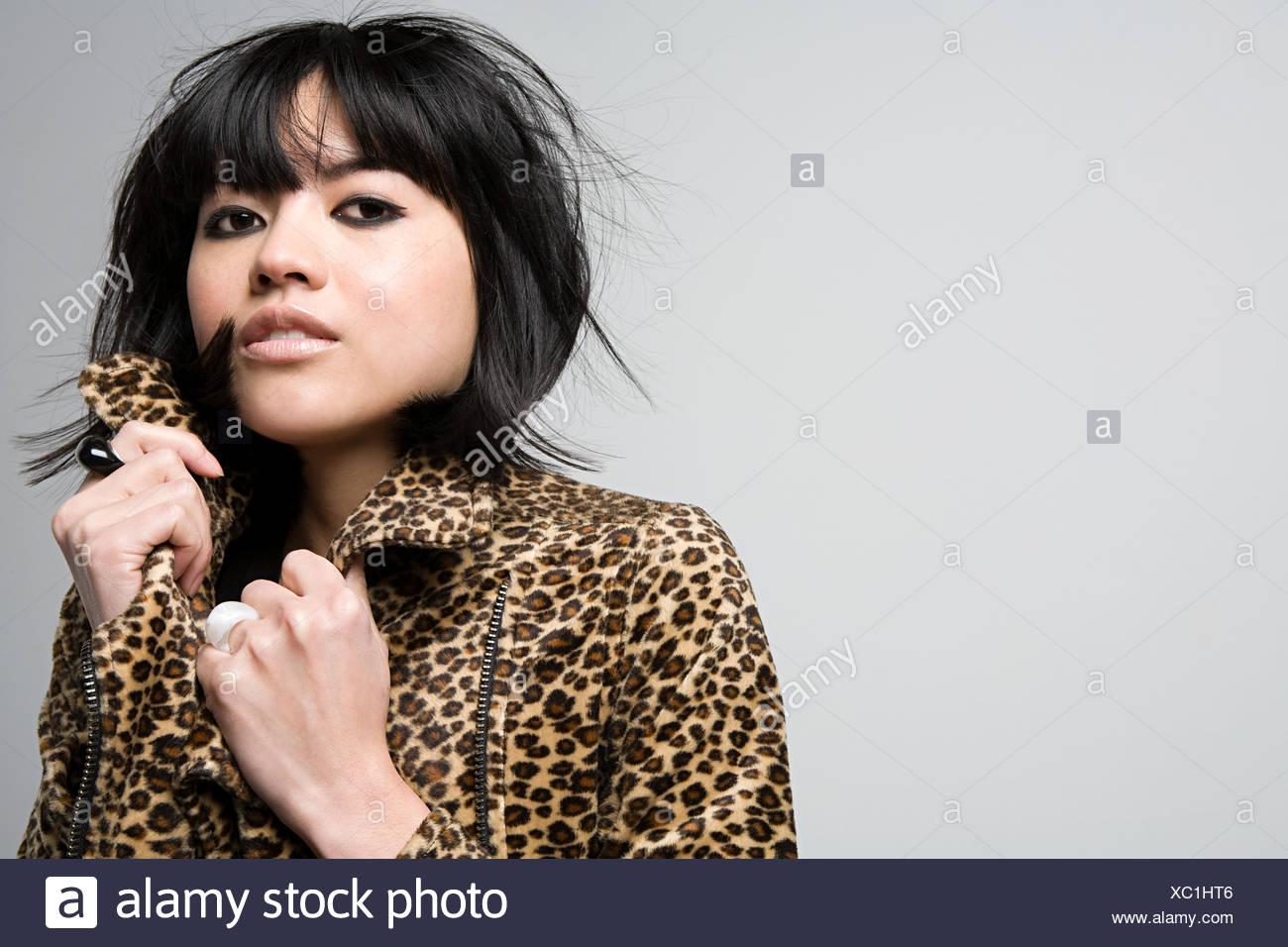Woman wearing a leopard skin jacket - Stock Image