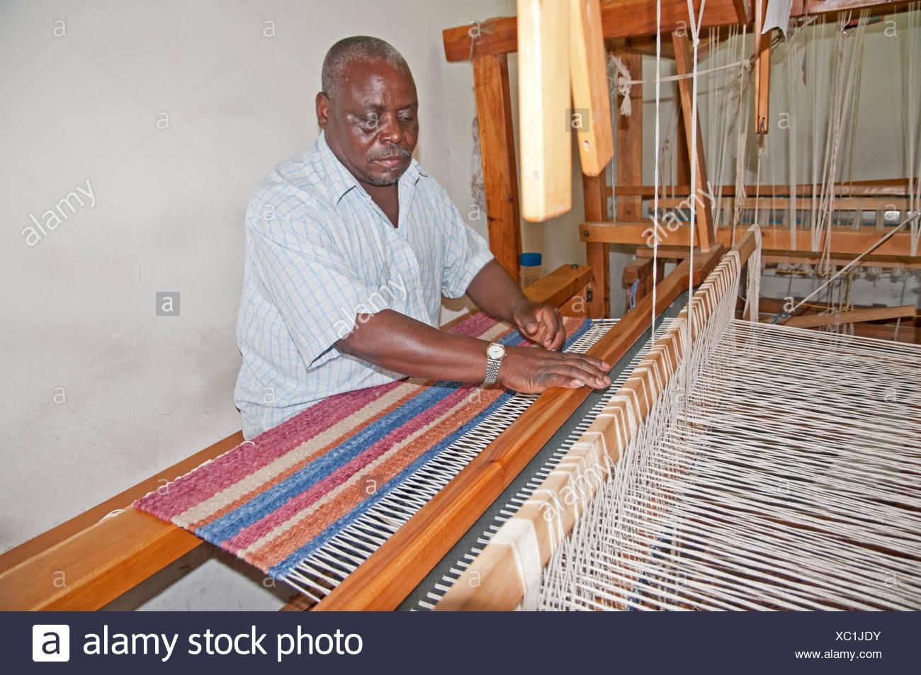 Black African man weaving a woollen rug on loom at Elmentieta Weavers on Lake Road Naivasha Kenya Africa  LOOM WEAVE WEAVER RUG - Stock Image