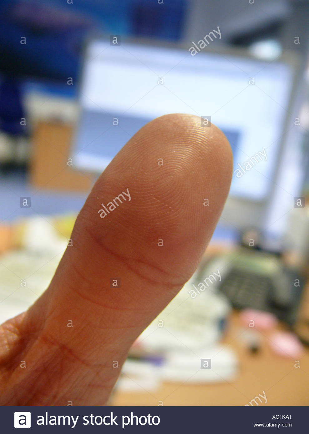 thumb in front of a computer monitor - Stock Image