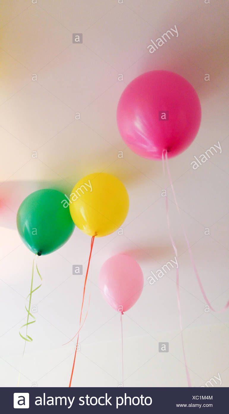 Low Angle View Of Colorful Balloons Against Ceiling At Home - Stock Image