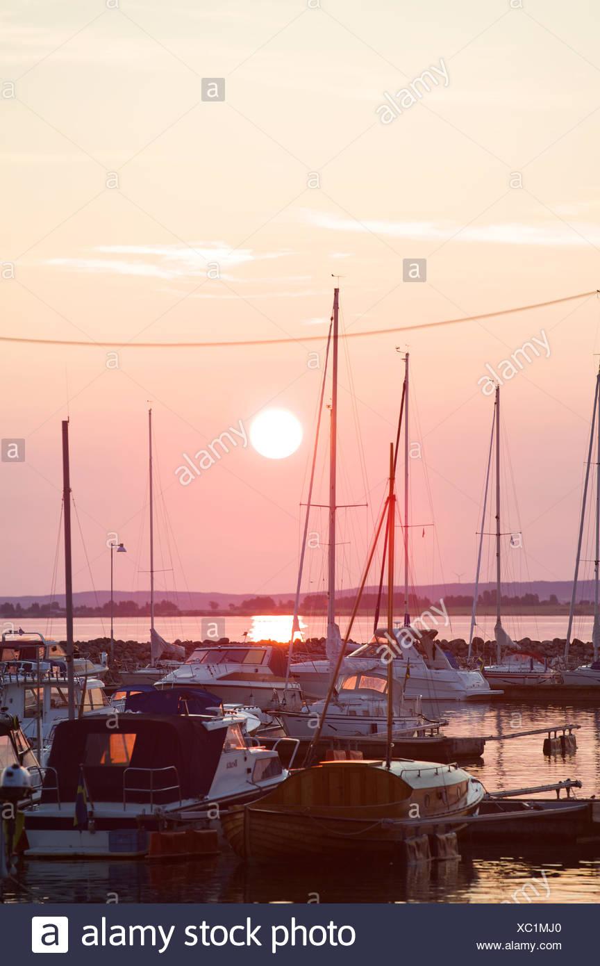 Sweden, Smaland, Granna, Anchored yachts at sunset - Stock Image