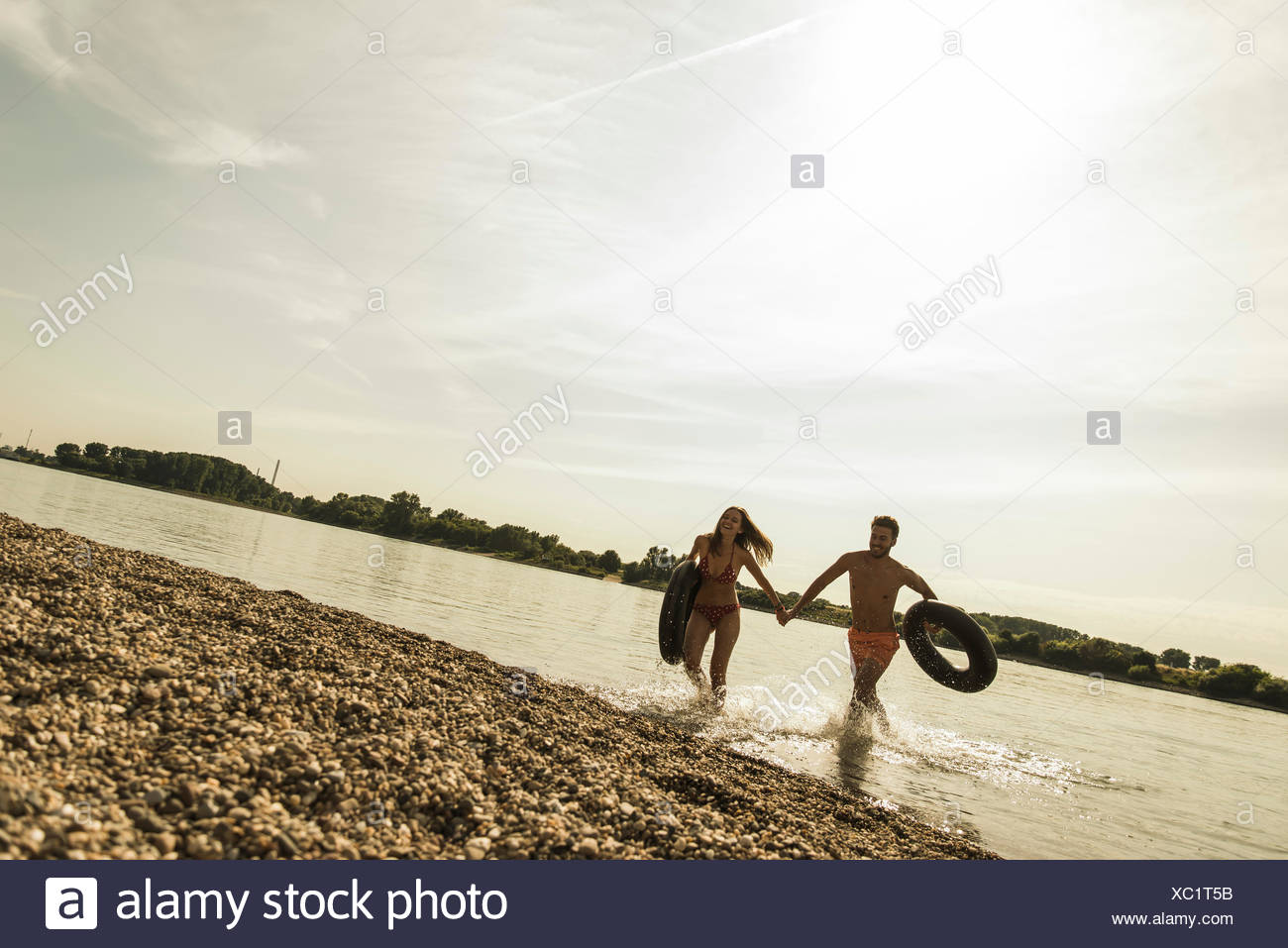 Young couple running with inner tubes in river - Stock Image