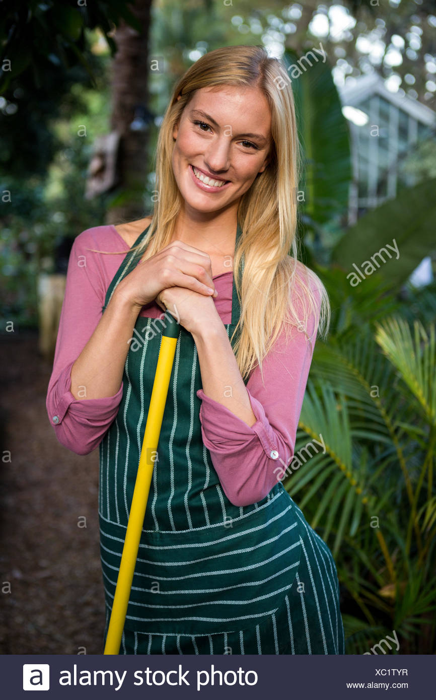 Portrait of attractive gardener with hand tool at garden - Stock Image