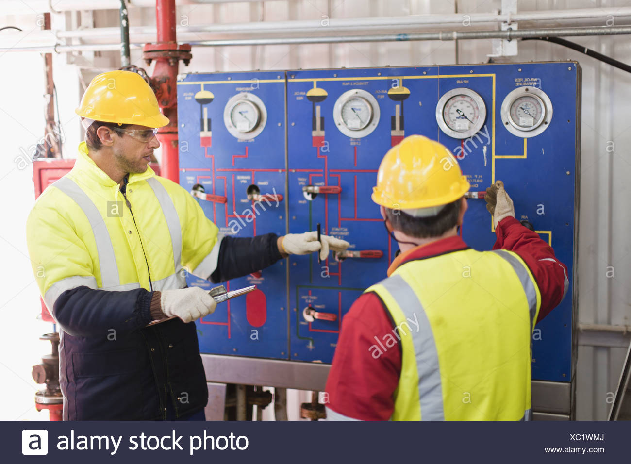 Workers checking gauges on oil rig - Stock Image
