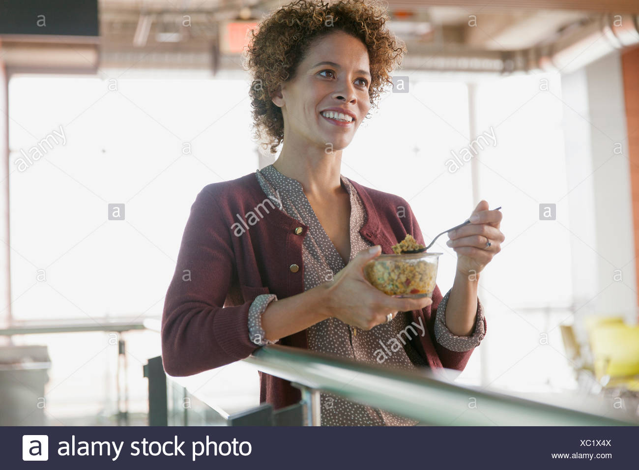 Woman snacking at office. - Stock Image