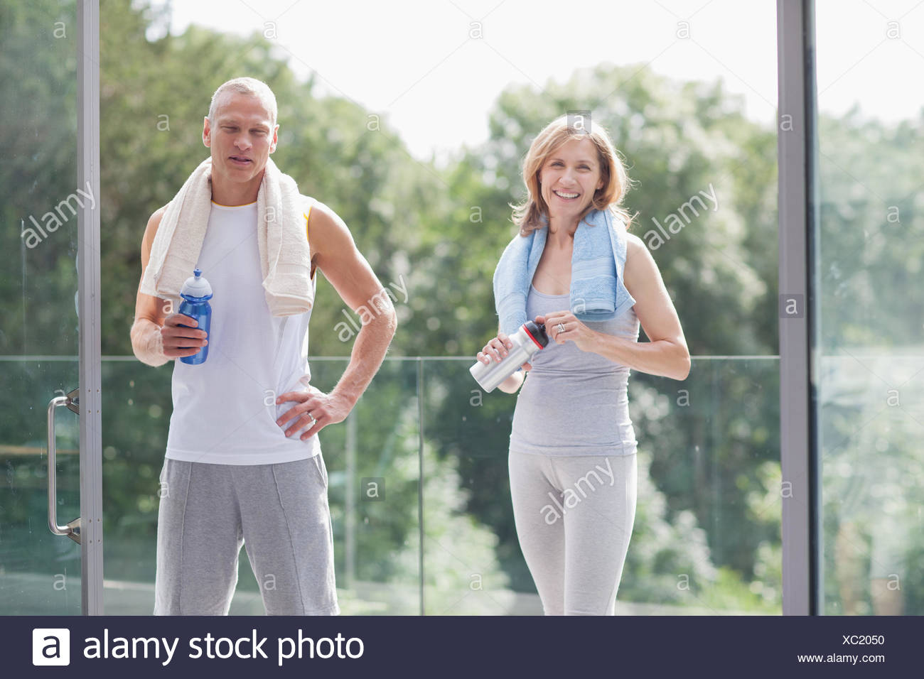 Couple standing with towels and water bottles - Stock Image