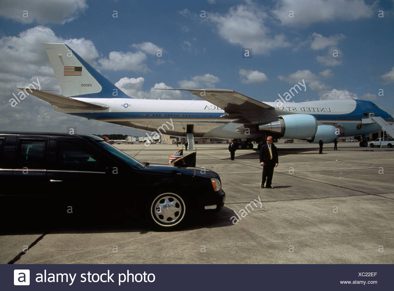 Air Force One awaits arrival of President Bush in his limousine. - Stock Image