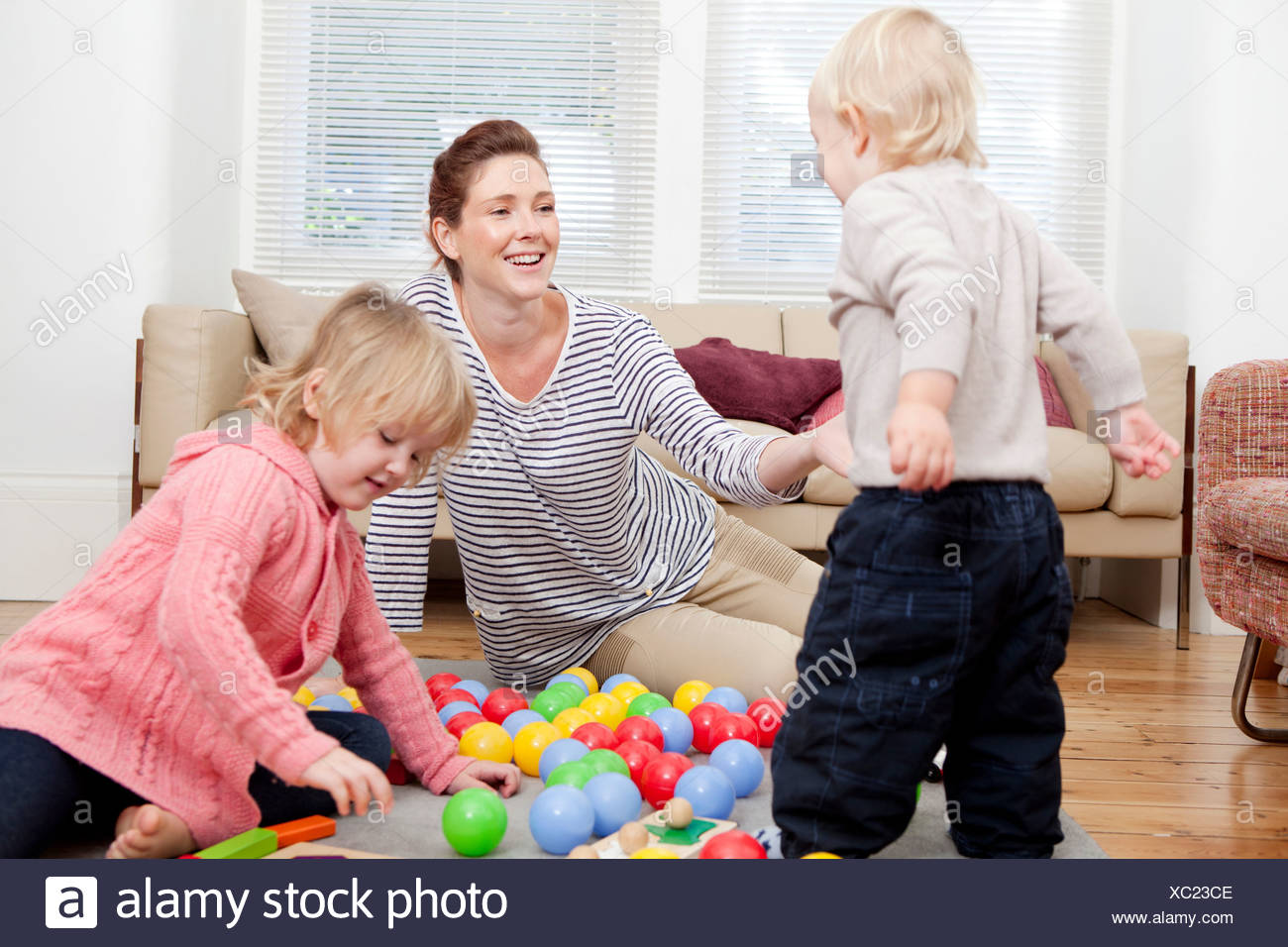 Mother and children playing with plastic balls - Stock Image