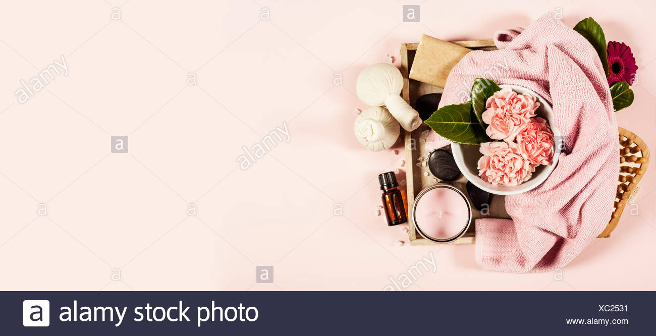 Spa background with sea salt, bowl ,flowers, water, soap bar, candles, essential oils, massage brush and flowers,top view. Flat lay. Pink background - Stock Image