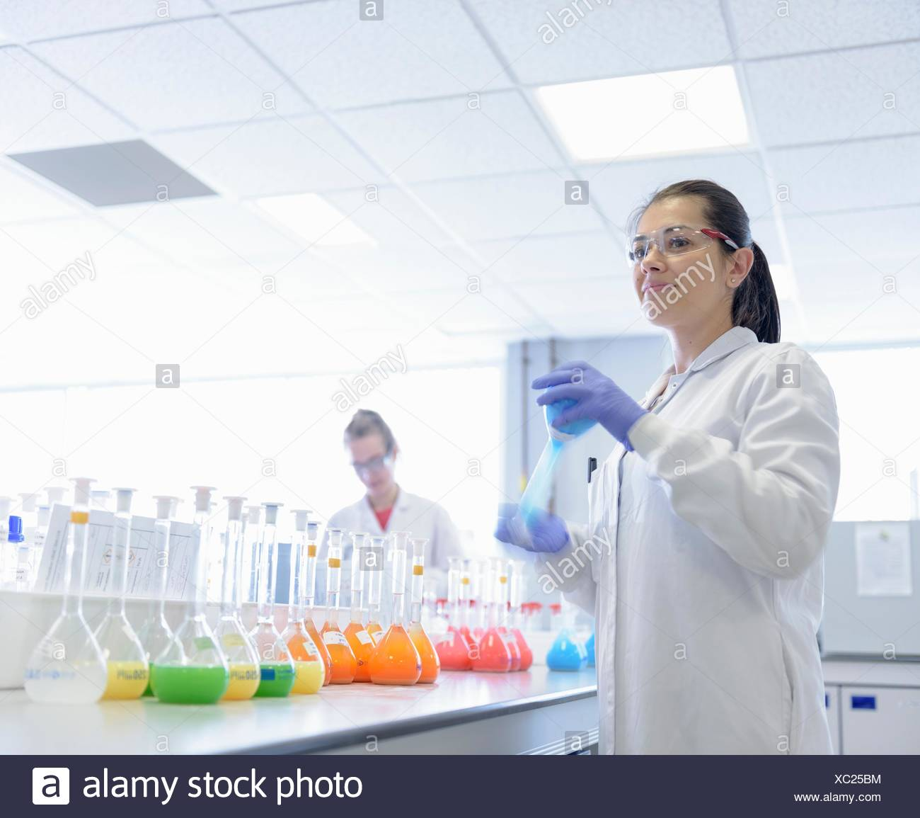 Scientist mixing food colouring in laboratory - Stock Image
