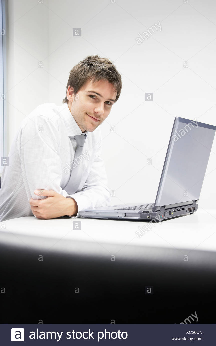 Contented Businessman sitting at desk with Laptop, portrait - Stock Image