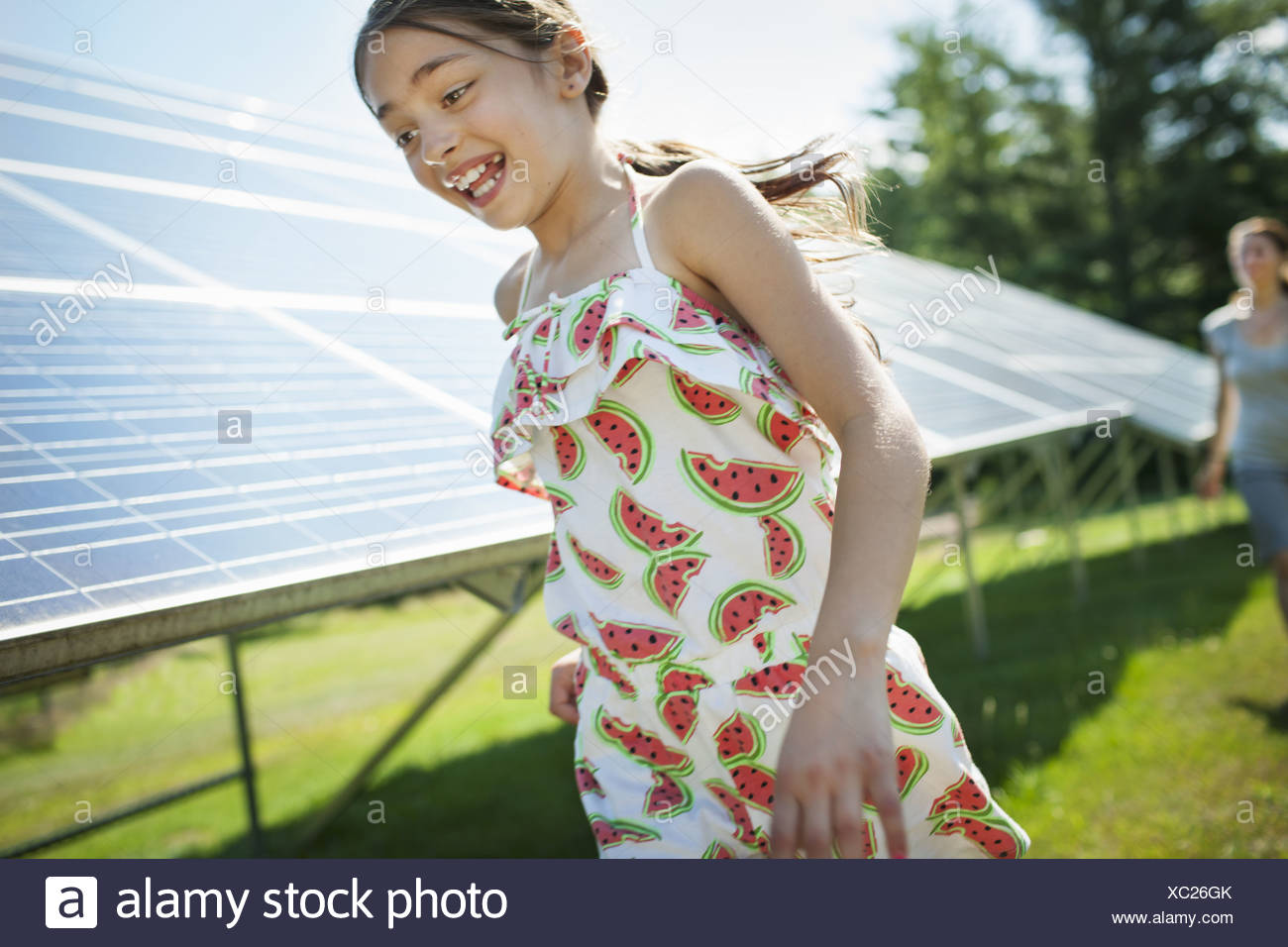 New York state USA child mother beside solar panels farm USA - Stock Image