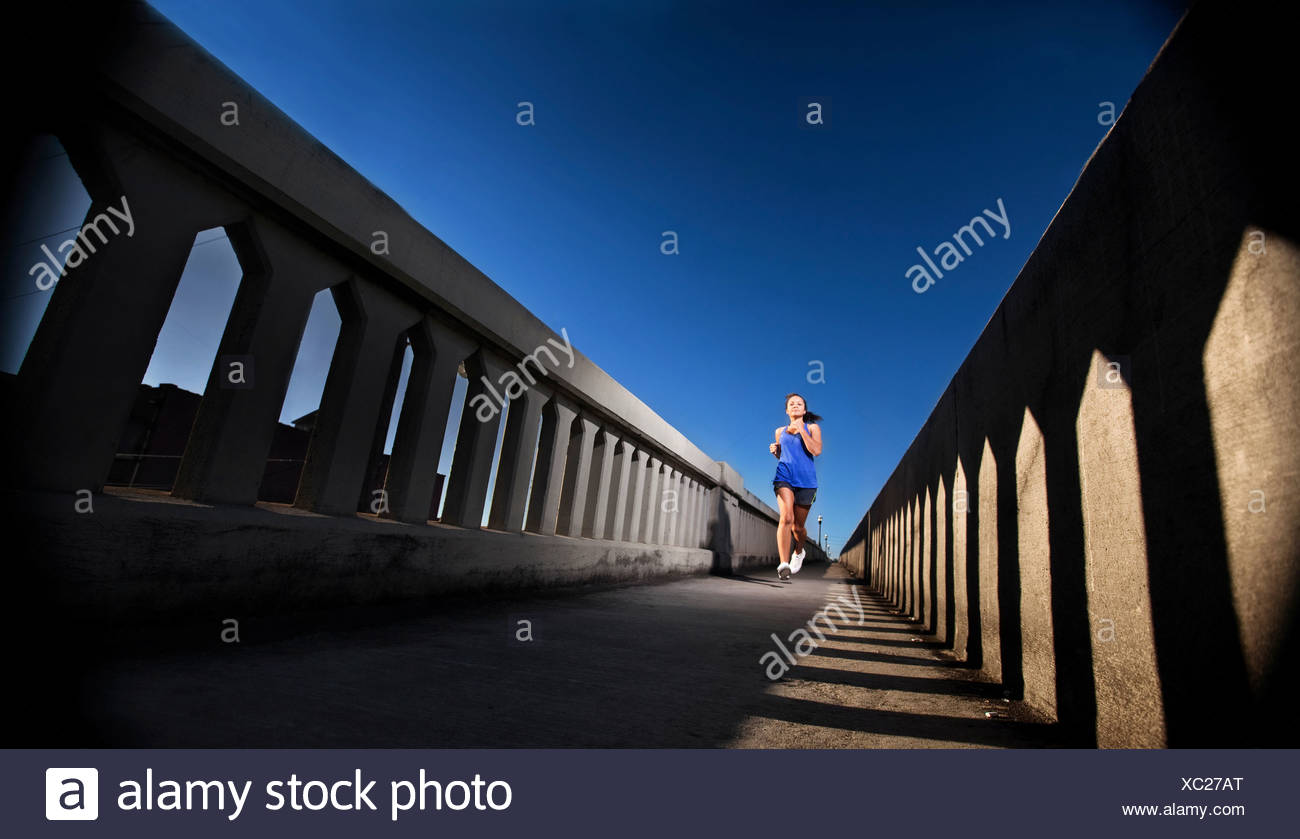 A teenage girl runs on the sidewalk of a bridge in downtown Birmingham, Alabama. - Stock Image