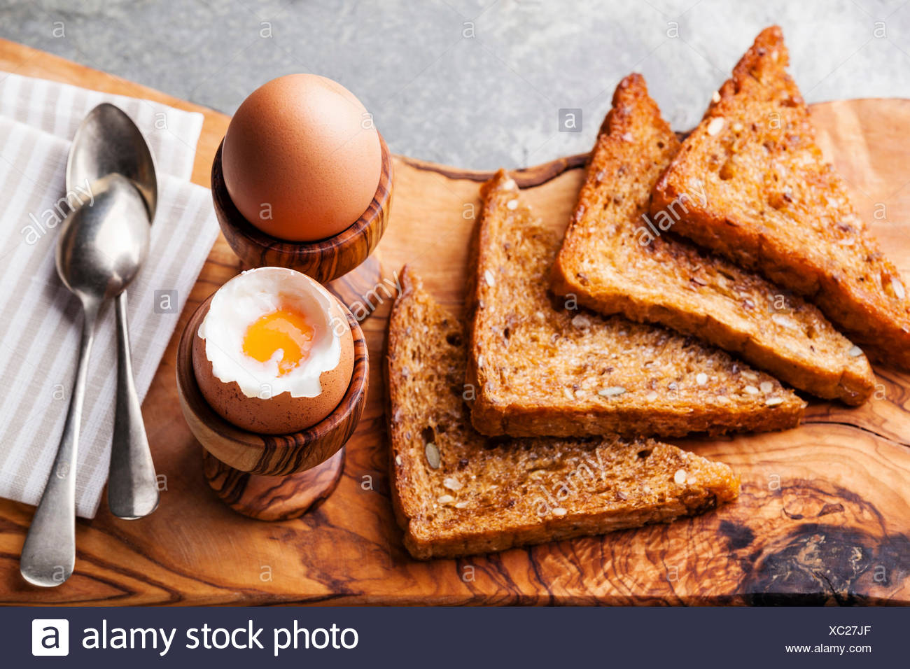 Boiled eggs for breakfast in olive wood egg cups - Stock Image