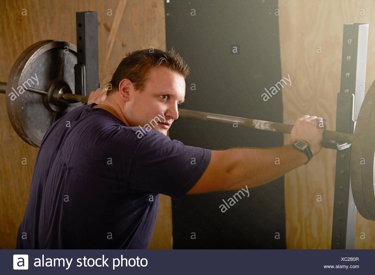 Young male weightlifter preparing to lift barbell in gym - Stock Image