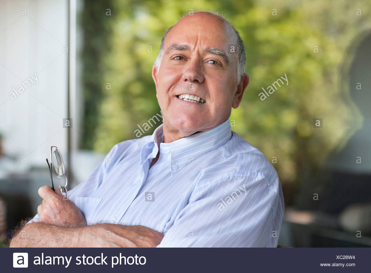 Smiling man with arms crossed - Stock Image