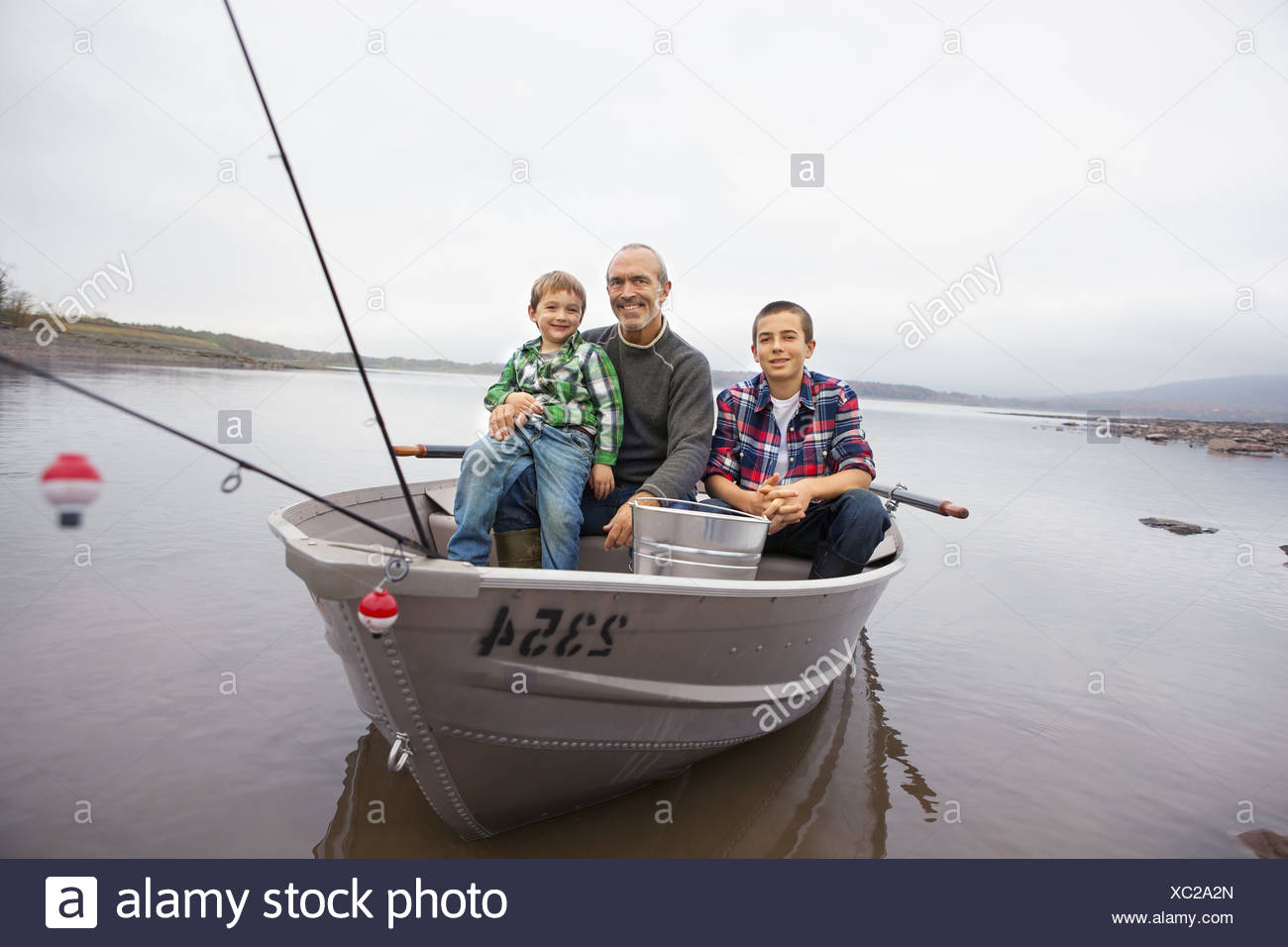 A day out at Ashokan lake. A man and two boys fishing from a boat. - Stock Image