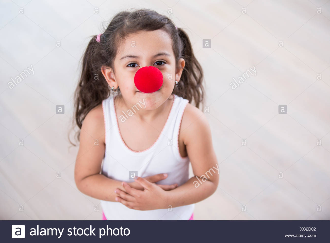 Portrait of cute little girl wearing clown nose at home - Stock Image
