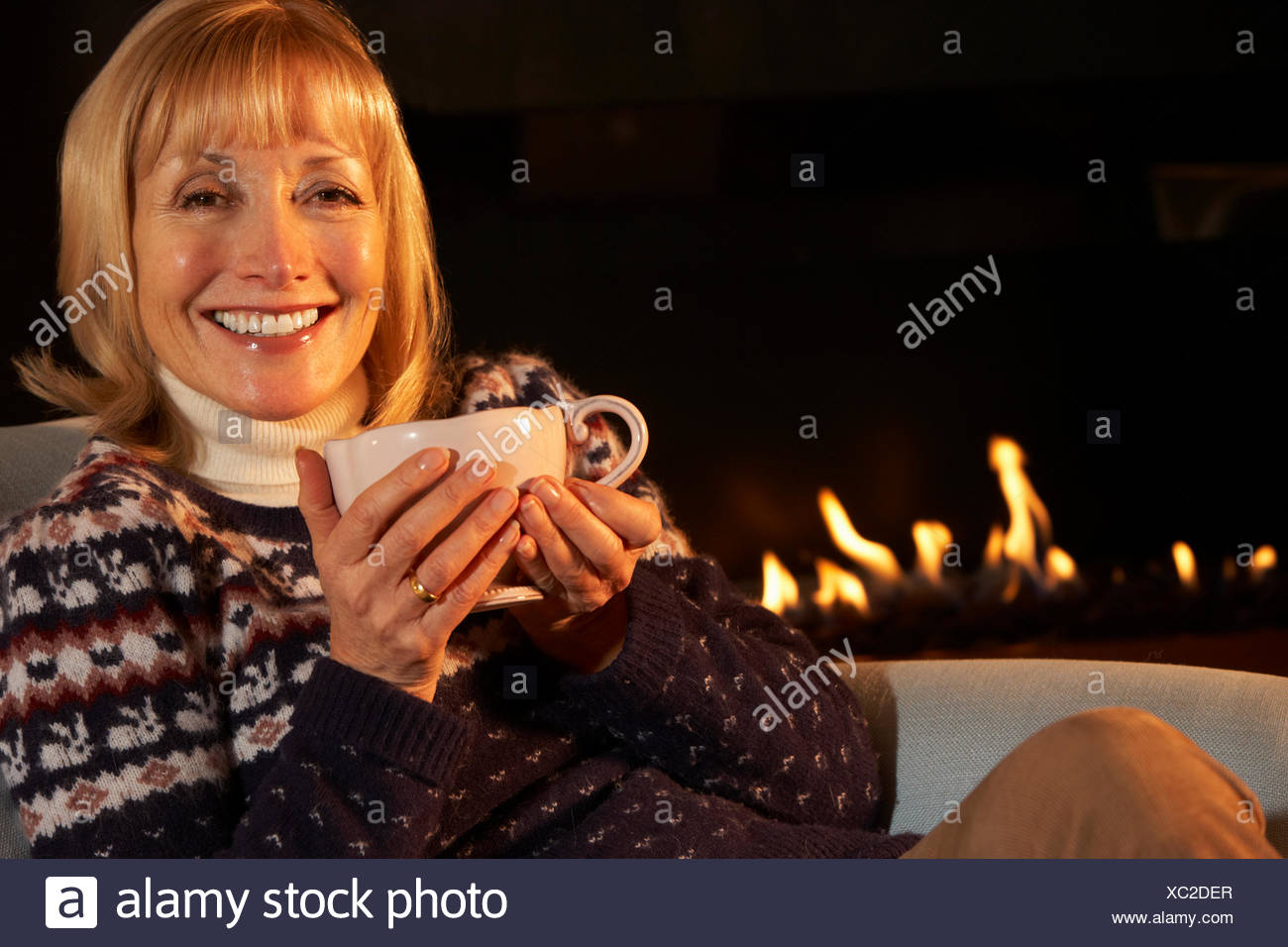 Mature woman relaxing in front of fire at home - Stock Image