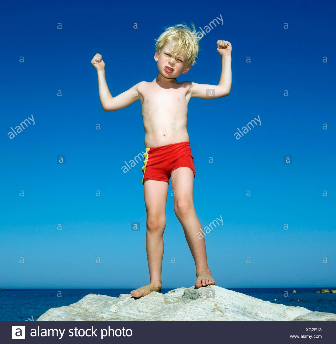 Young boy on large rock by the water flexing and scowling. - Stock Image