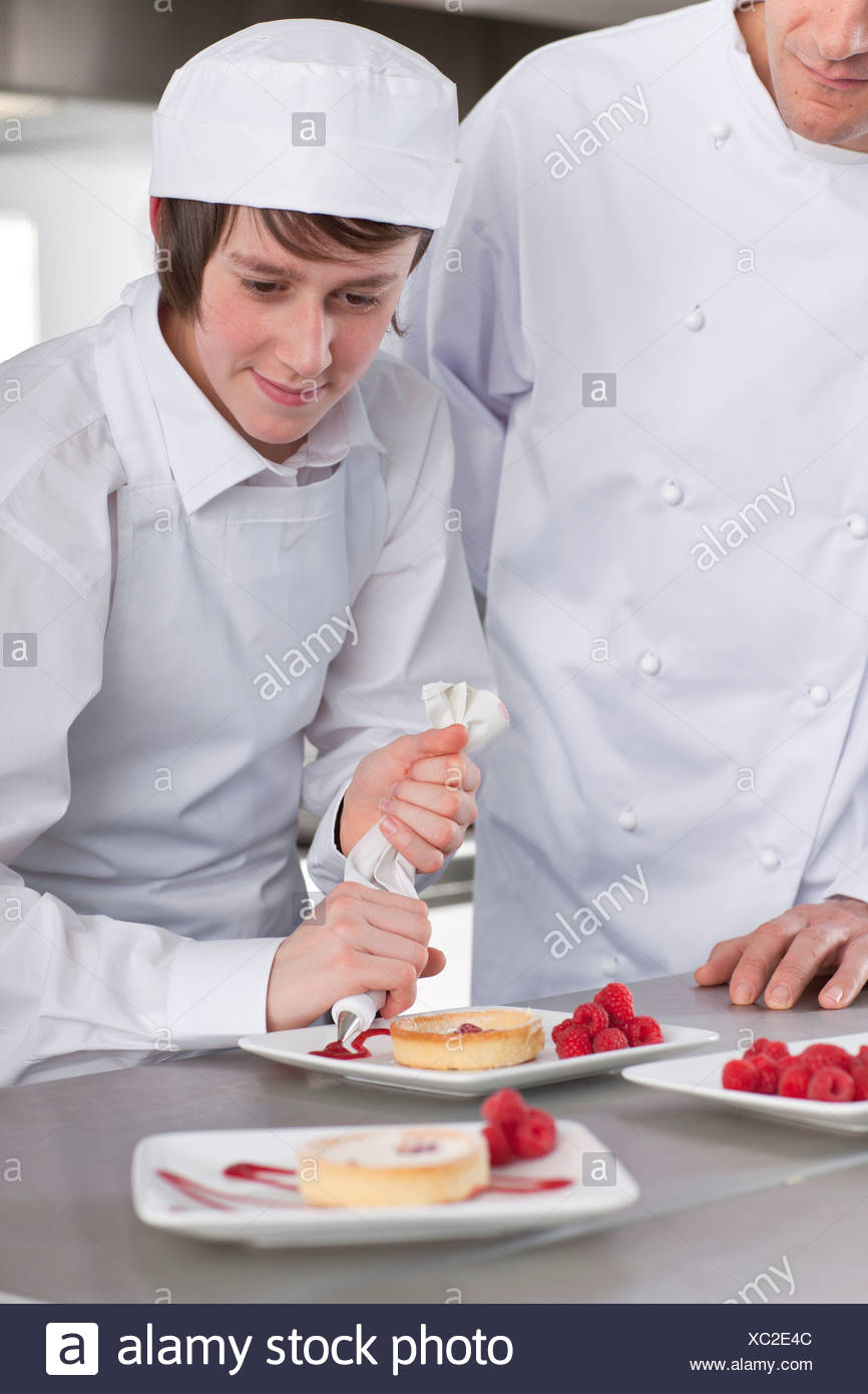 Chef teaching trainee how to garnish gourmet dessert in commercial ...