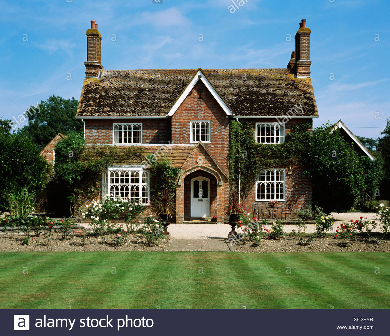 Victorian brick country cottage with mown striped lawn - Stock Image