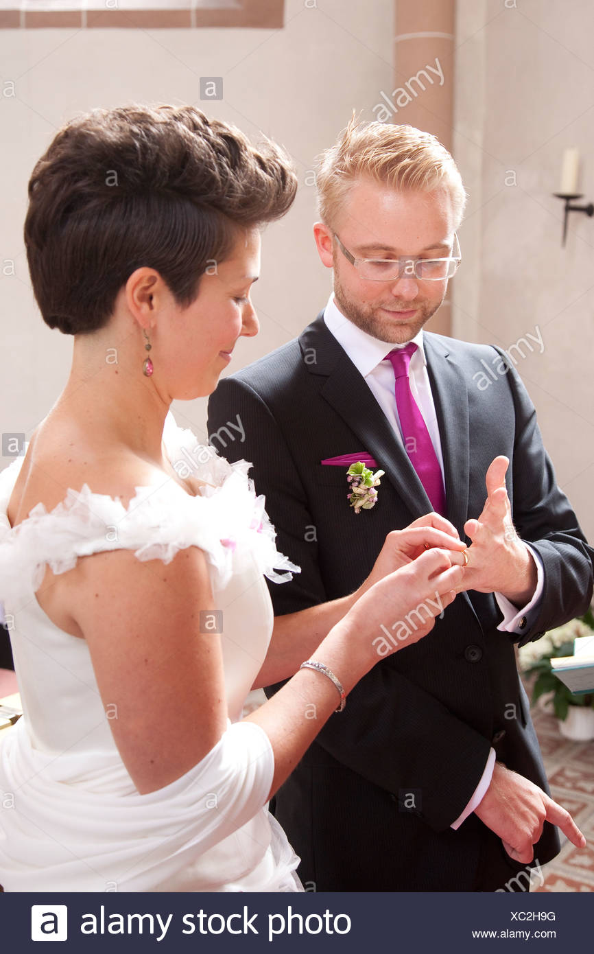 Bride and groom exchanging wedding rings during the church wedding, Regensburg, Bavaria, Germany, Europe - Stock Image