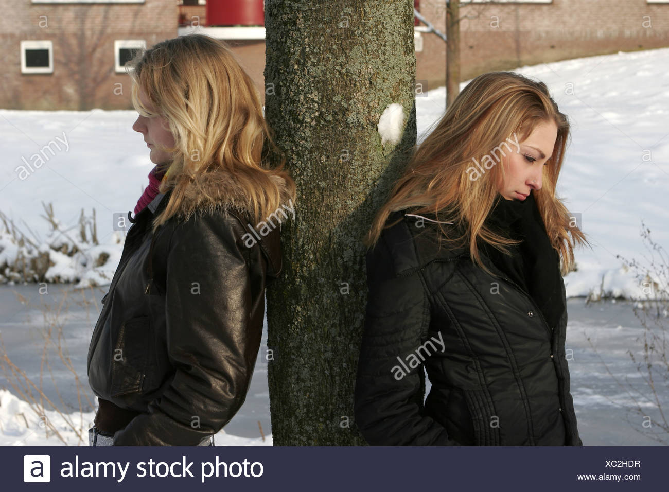 Teenage friends having an issue outside in winter standing back to back to back against tree contemplating - Stock Image