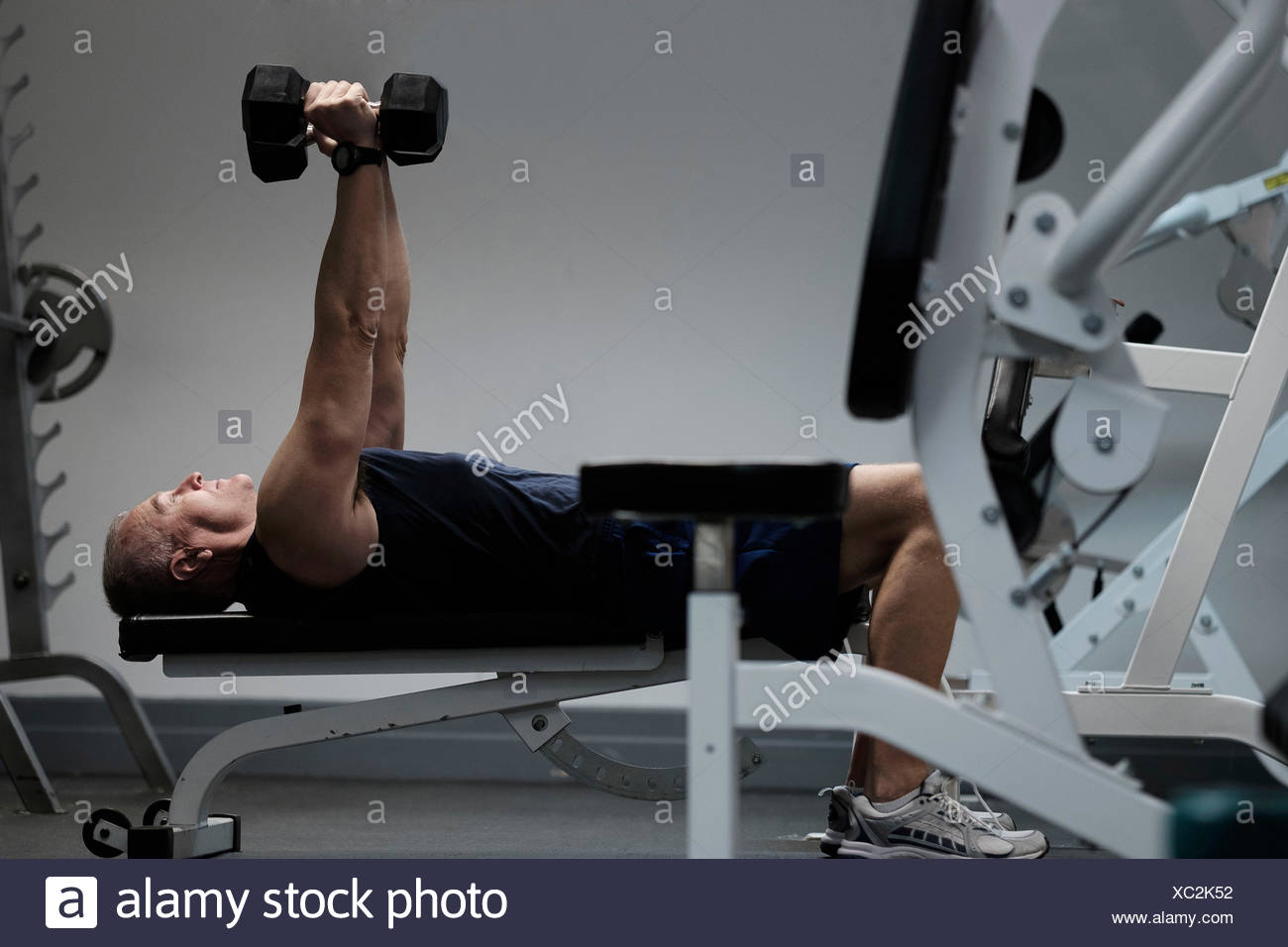 Man exercising with dumbbells on weight bench - Stock Image