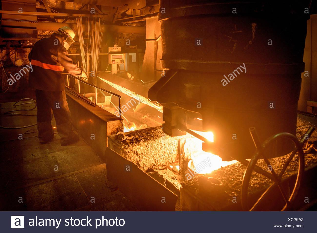 Steel worker attending furnace in steel foundry - Stock Image