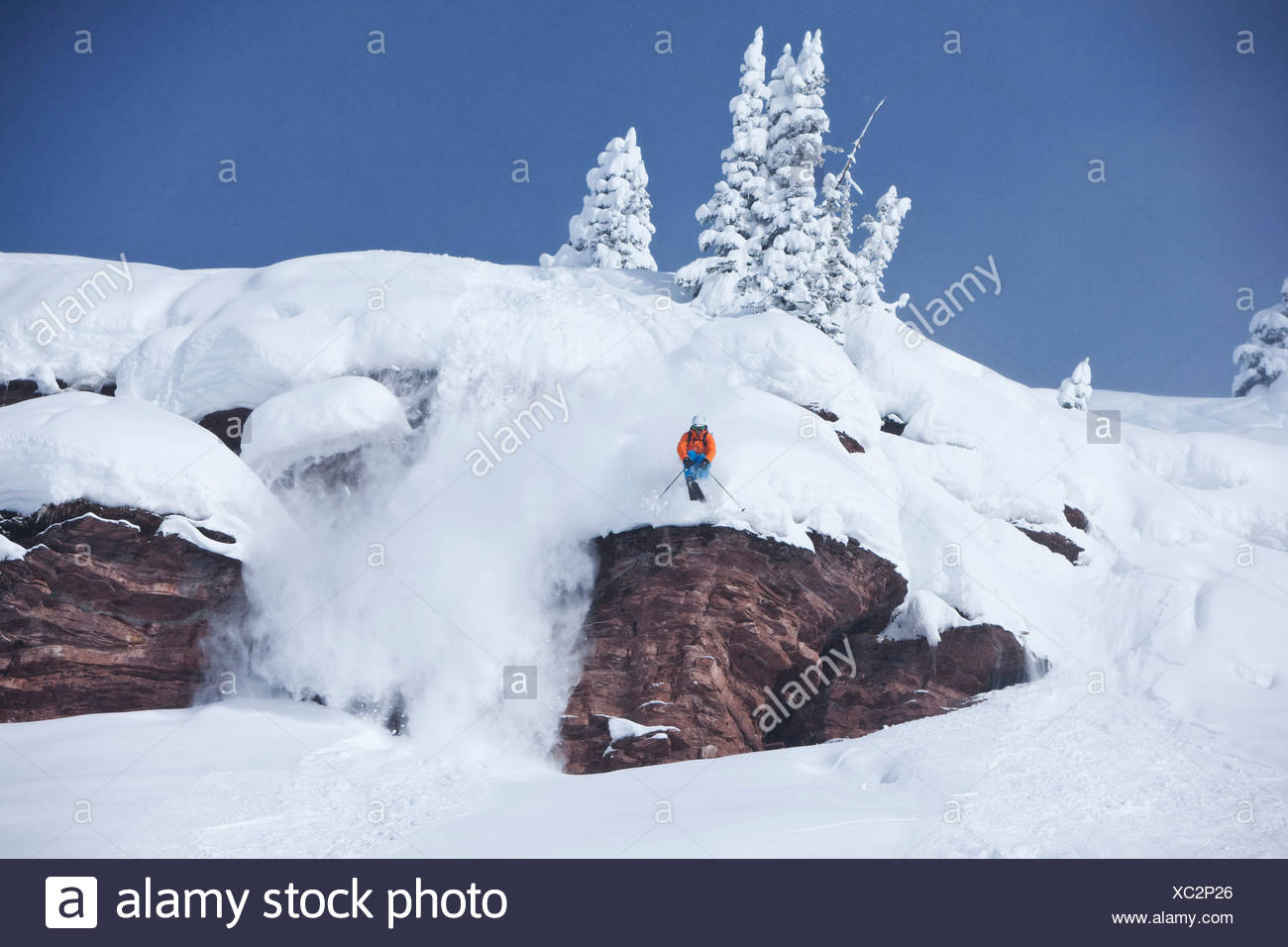 A athletic skier jumping off a cliff in the backcountry on a sunny powder day in Colorado. - Stock Image