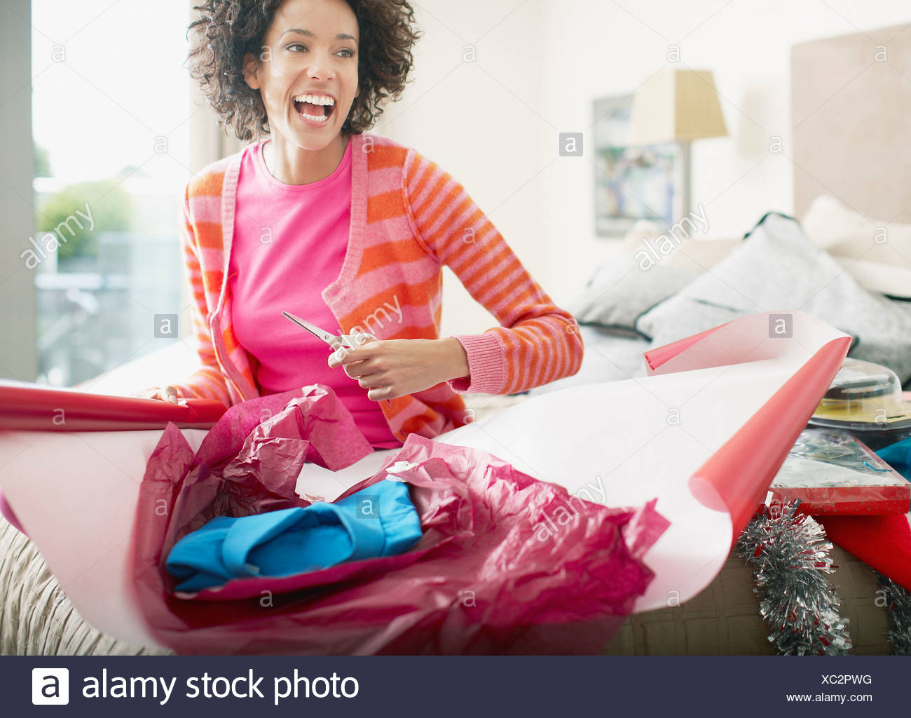 Woman wrapping Christmas gift - Stock Image