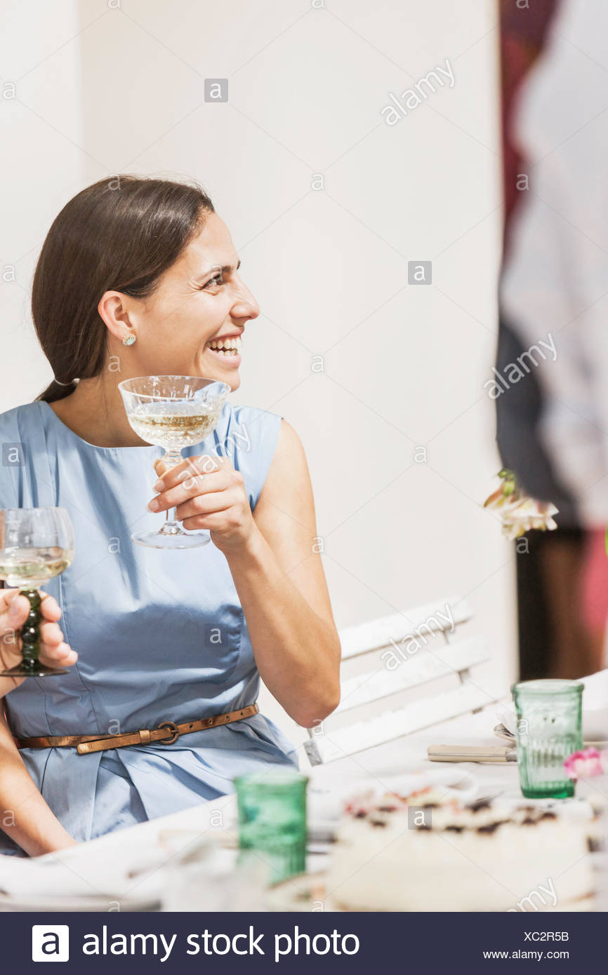 Young woman drinking wine at party - Stock Image
