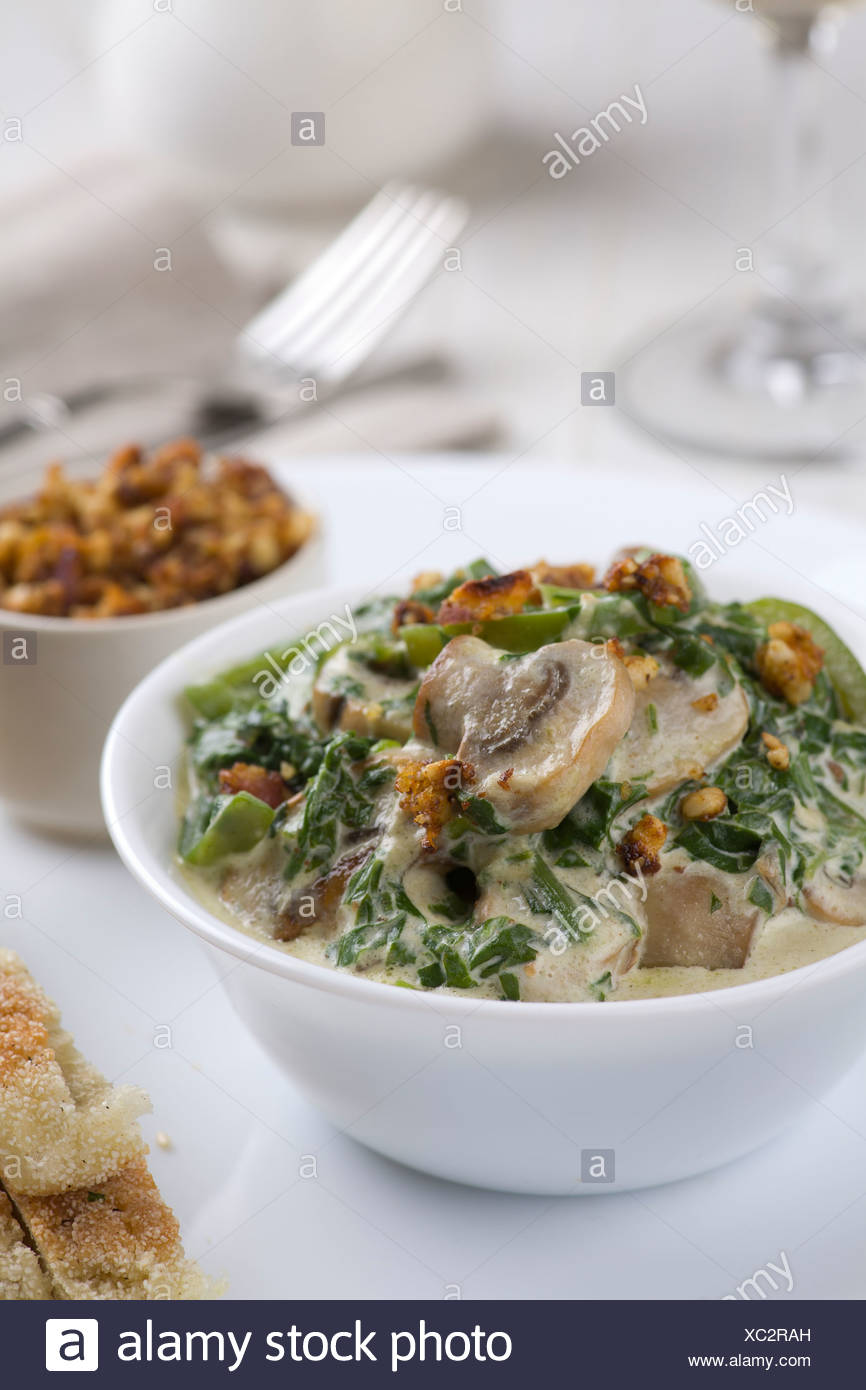 Mushrooms with spinach and green vegetables, served with nut crumble, and flatbread - Stock Image