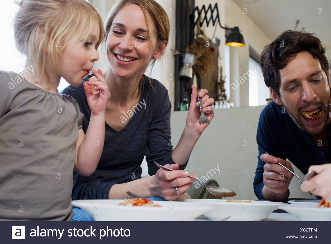 Mid adult parents and two daughters eating a spaghetti meal - Stock Image