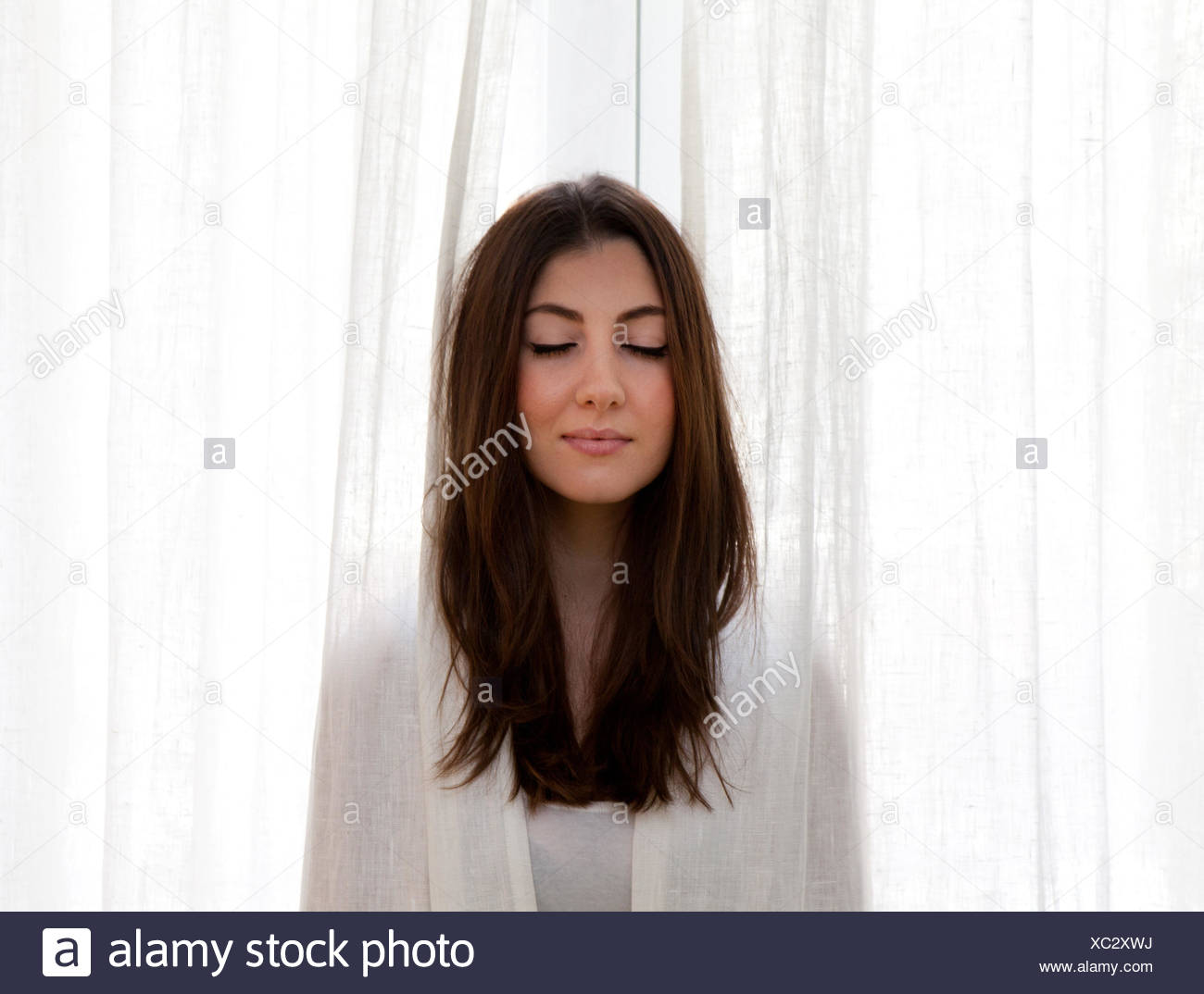 Young adult woman poking head out of curtains, eyes closed - Stock Image