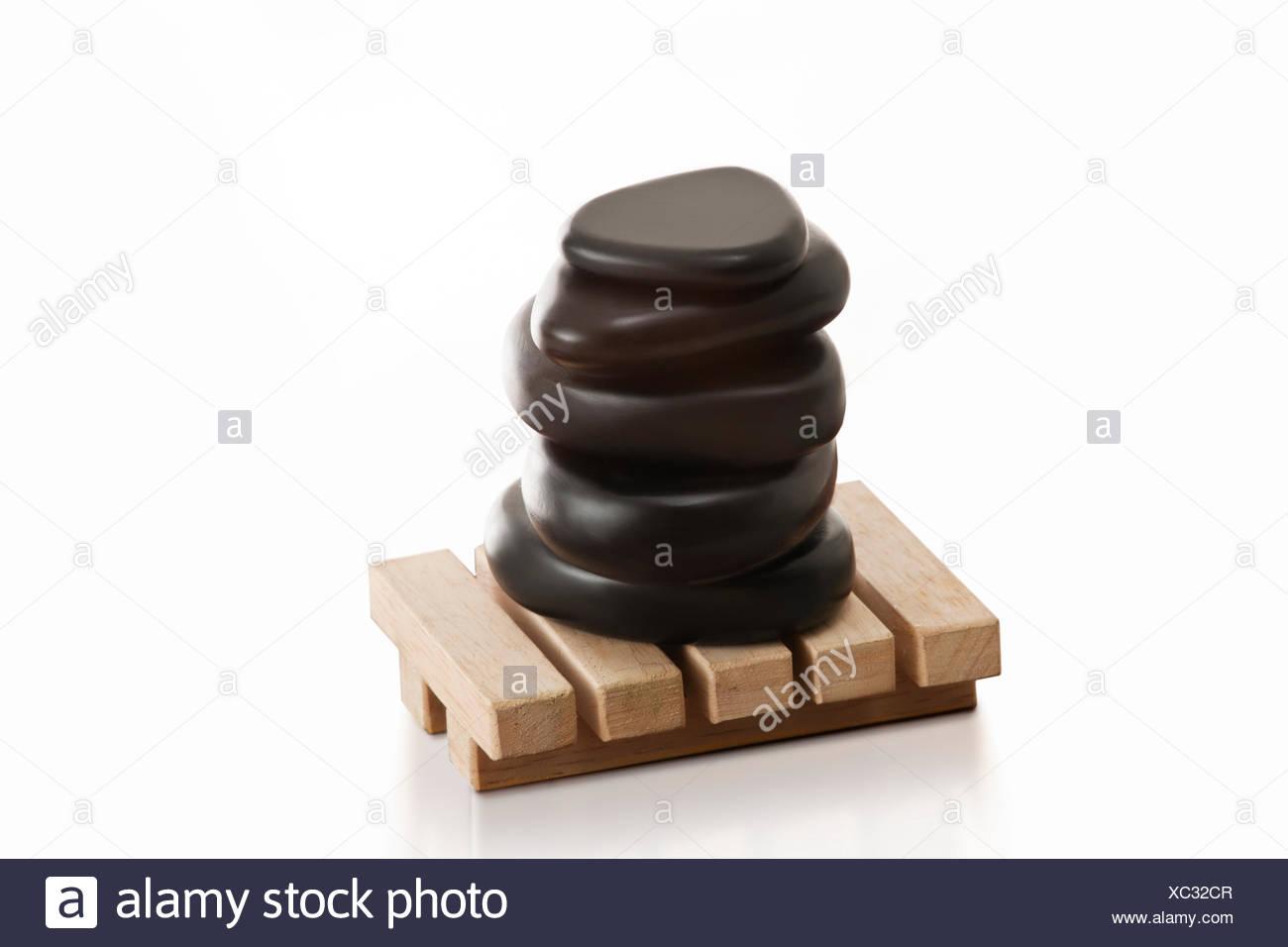 Stacked massage stones on wooden base - Stock Image