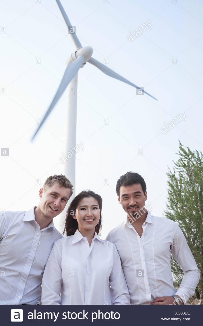 Portrait of three young business people standing in front of a wind turbine, looking at camera - Stock Image