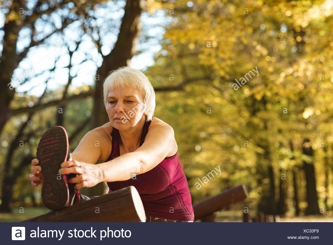 Senior woman performing stretching exercise in the park - Stock Image