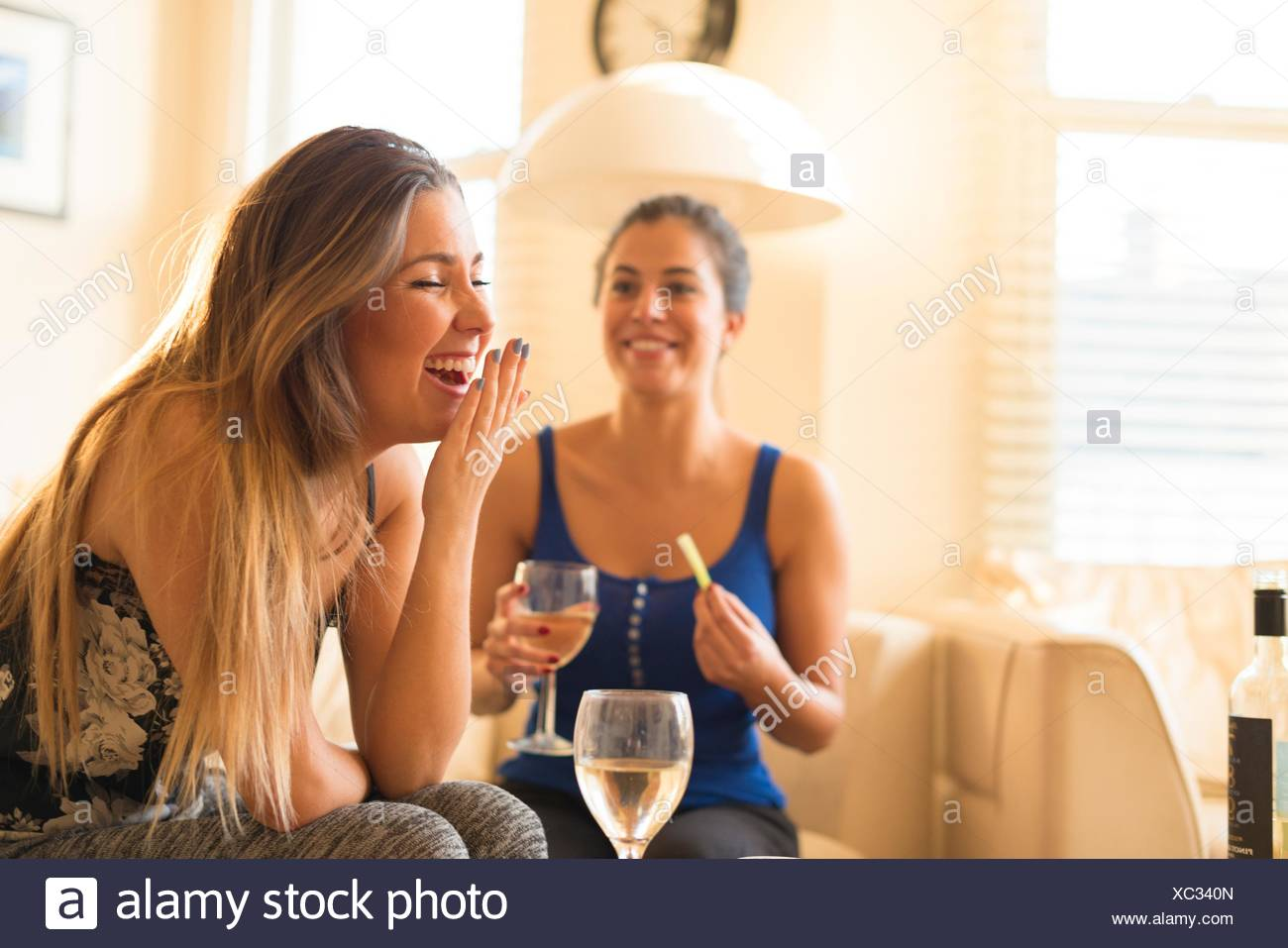Two young woman having girls night in, drinking and laughing Stock Photo