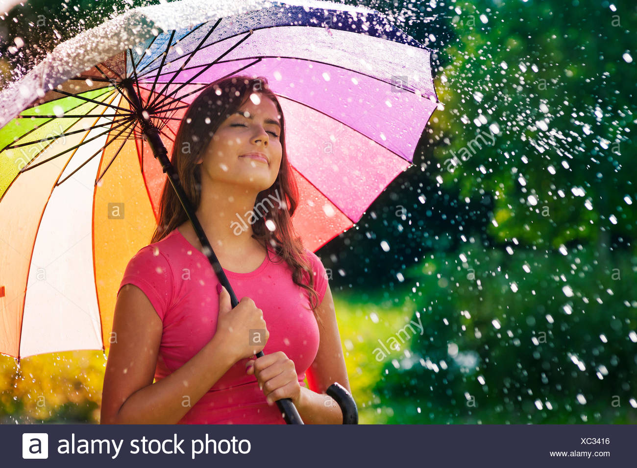 Young woman breathing fresh air during the spring rain  Debica, Poland - Stock Image